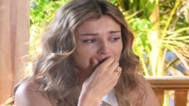 Ester chorando com a mão nos lábios