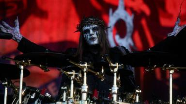 Joey Jordison de máscara e figurino, com os braços abertos, atrás da bateria