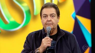 Faustão segurando o microfone durante apresentação do Domingão na Globo
