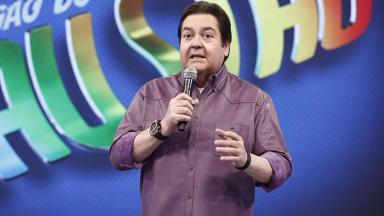 O apresentador Fausto Silva segundo um microfone no palco do seu programa na Globo