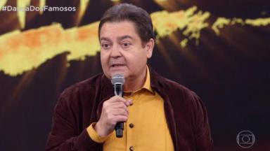 Faustão de camisa social laranja, casaco e microfone na mão