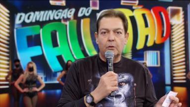 Faustão segurando o microfone no palco do Domingão