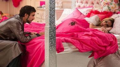 Leozinho debruça sobre a cama e observa aranha em cima de Fedora que dorme