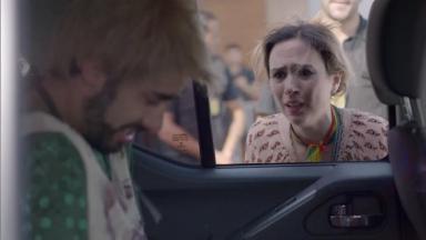 Leozinho dentro do carro da polícia de cabeça baixa enquanto que Fedora se despede com tristeza