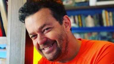Fernando Rocha sorrindo de camiseta laranja