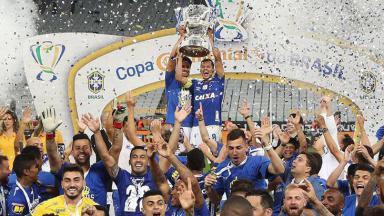 Jogador do Cruzeiro erguendo a taça