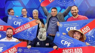 """Flávio Bolsonaro segura placa de """"CPF cancelado"""" com o irmão, Eduardo Bolsonaro, e o apresentador Sikêra Jr."""