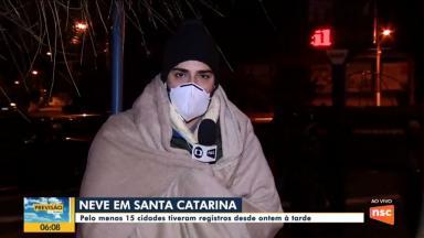 Repórter enrolado em cobertor em link ao vivo, segurando o microfone