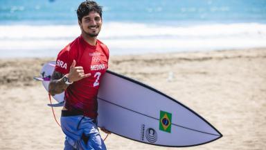 Gabriel Medina fazendo sinal de positivo com a prancha na mão