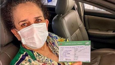 Gal Costa segurando a carteira de vacinação