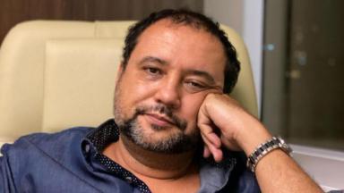 Geraldo Luís com a mão no rosto e de relógio no pulso esquerdo