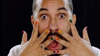 Gil do Vigor posado com cara de assustado com as mãos próximas à boca