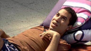 Gilberto está deitado em almofadas na área externa do BBB21 com a mão no peito e conversando