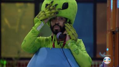 Gilberto com o big fone no ouvido fantasiado de alienígena no BBB21