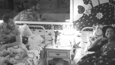Camilla de Lucas rindo enquanto Gilberto está sentado na cama