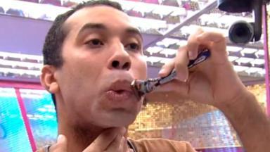 Gilberto fazendo a barba no banheiro do BBB21 com um aparelho de barbear na mão