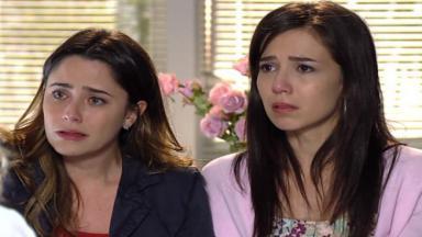 Ana e Manu lado a lado escutando o médico, apreensivas