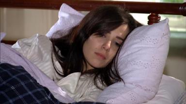 Cena de A Vida da Gente com Manuela deitada com cara de deprimida