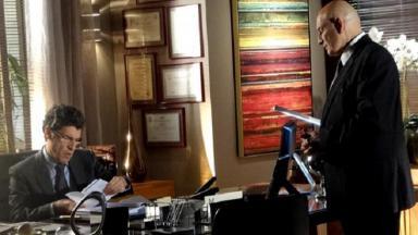 Cena de A Vida da Gente com Jonas sentado em sua mesa lendo um documento e um funcionário, de frente, em pé
