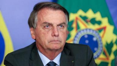 Bolsonaro sentado e com expressão de seriedade