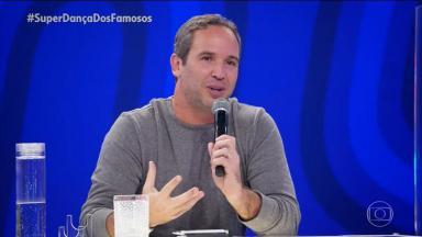 Caio Ribeiro, no palco do júri da Super Dança dos Famosos, segurando um microfone sentado e com um copo de água na frente