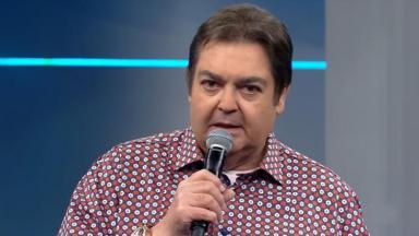 Faustão segurando microfone no palco do seu programa na Globo