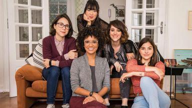 As cinco protagonistas de As Five, abraçadas e sorrindo, de pé, posam para foto