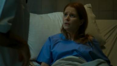 Mônica deitada no hospital da prisão em cena de Pega Pega