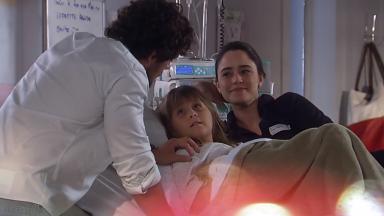Júlia deitada na cama do hospital com Ana falando com Rodrigo que está de pé