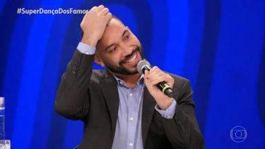 Gil do Vigor no palco da Super Dança dos Famosos segurando o microfone com uma mão, a outra coçando a testa e sorrindo