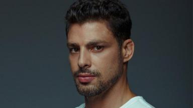 o ator Cauã Reymond, com barba, olhando para foto sério