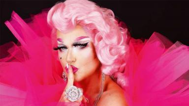 Xuxa vestida de drag queen colocando o dedo na boca