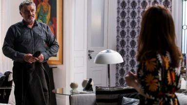 Guido em pé, segurando o paletó, olha emocionado para Shirlei