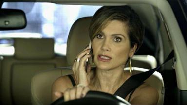 Helena dentro do carro falando ao celular