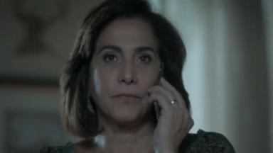 Heleninha com cara séria leva o celular até o ouvido