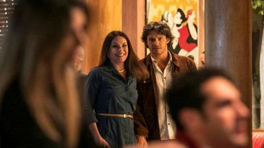Henrique com Penélope na porta do restaurante observam Beto e Tamara à mesa