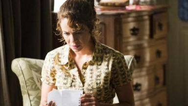 Cena de Império com Cristina sentada lendo uma carta