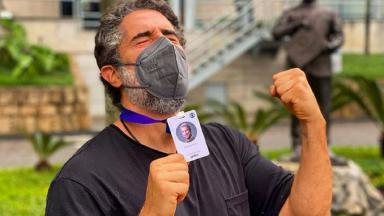 Marcos Mion com crachá da Globo na mão