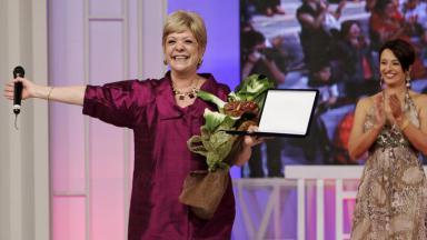 Ione de vestido rosa escuro segurando microfone e um prêmio