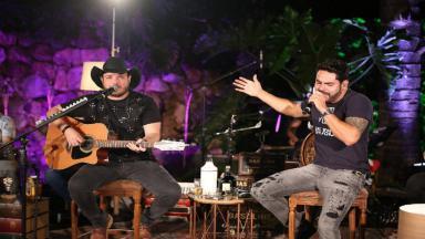 A dupla Israel e Rodolffo durante apresentação sentados em uma cadeira. Israel toca violão e Rodolffo segura o microfone para cantar