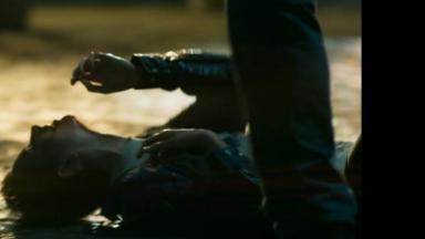 Ivana está caída no chão e tenta se proteger com as mãos enquanto leva chutes