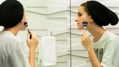 Ivana passando a gilete no rosto em frente ao espelho