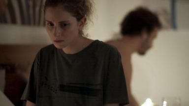 Ivana está sentada na cama e pensativa com Cláudio ao fundo