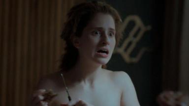 Assustadada, Ivana com tesoura na mão, cortando os cabelos em frente ao espelho