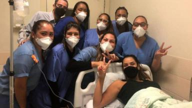 Ivy Moraes, em leito hospitalar, posa com técnicas de enfermagem do hospital