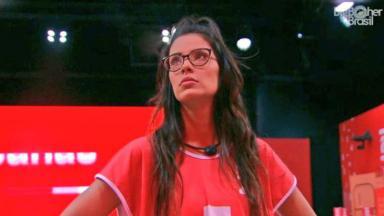 Ivy Moraes de colete vermelho e óculos
