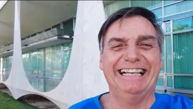 Presidente Jair Bolsonaro posa para foto, sorrindo, no Palácio do Planalto