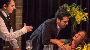 Beto se inclina e coloca a mão no peito de Tancinha que está passando mal
