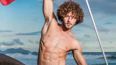 O ator João Gana sem camisa com uma praia ao fundo