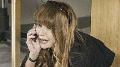 Alexia/Josimara fala ao celular enquanto está debaixo da mesa